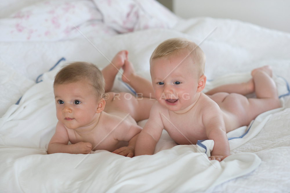 twin baby boys naked on their stomachs on a bed