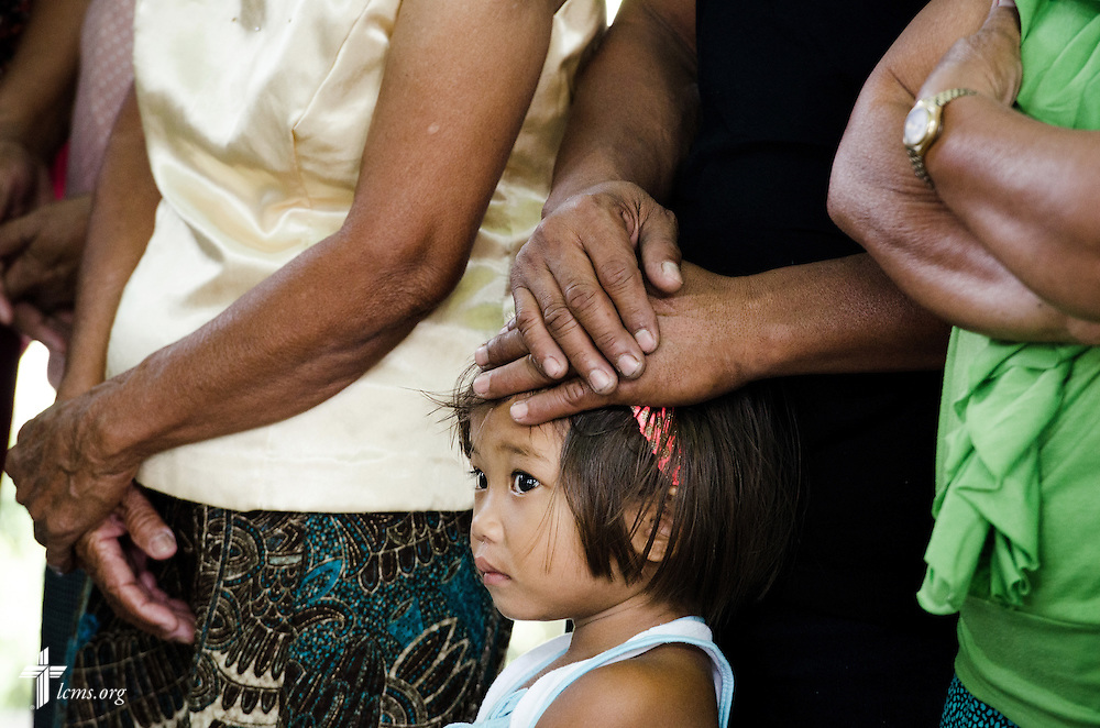A young girl waits with her family during communion at Christ Lutheran Church in Mahayag, Leyte Province, Philippines, on Sunday, March 16, 2014. LCMS Communications/Erik M. Lunsford