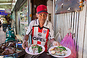 09 JULY 2011 - BANGKOK, THAILAND: A food hawker plates up orders of food at his stand in an alley in the Chinatown section of Bangkok, Thailand. Chinatown is the entrepreneurial hub of Bangkok, with thousands of family owned businesses selling wholesale merchandise in everything from food like rice, peanuts and meats, to dry goods like toys and shoes.  PHOTO BY JACK KURTZ