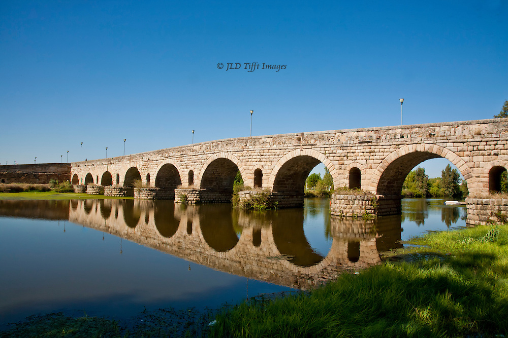 Ancient Roman bridge over the Guadiana River, Merida, Spain.  It has been kept in good repair and traffic still uses it. Its perfect hemicycles are perfectly reflected in the river as a mirror.