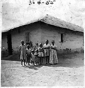 Children at a family's tin-roofed house in the Makina section of Kibra. This style of roofing is called 'debe' and can be found on Nubian houses across Kenya.  (1955)