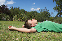 Boy (10-12) lying on grass listening to mp3 player