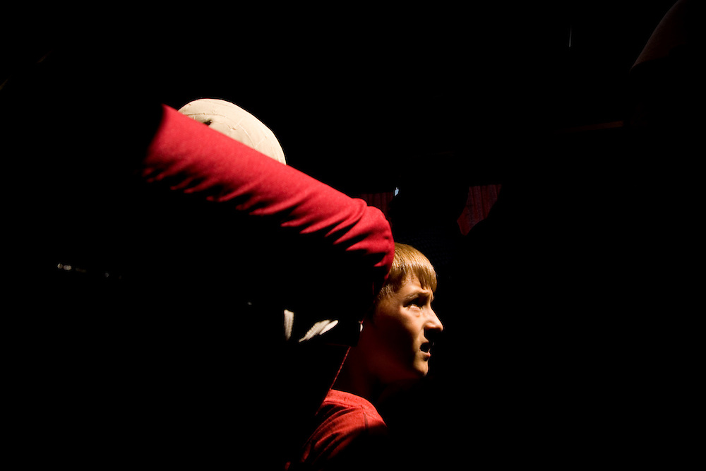 A young boy illuminated by a sunbeam from an overhead vent on the inter-city bus to Pristina...Mitrovica, Kosovo, Serbia.