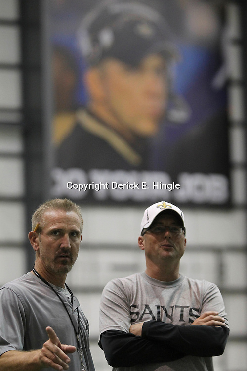 July 27, 2012; Metairie, LA, USA; A sign of New Orleans Saints head coach Sean Payton who was suspended by NFL commissioner Roger Goodell is seen over defensive coordinator Steve Spagnuolo and offensive coordinator Pete Carmichael following a training camp practice at the team's indoor practice facility. Mandatory Credit: Derick E. Hingle-US PRESSWIRE