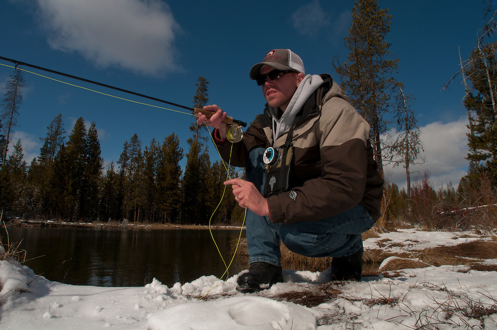 A fisherman cast to a rising trout while fishing the bank of the Fall River in Oregon during winter.