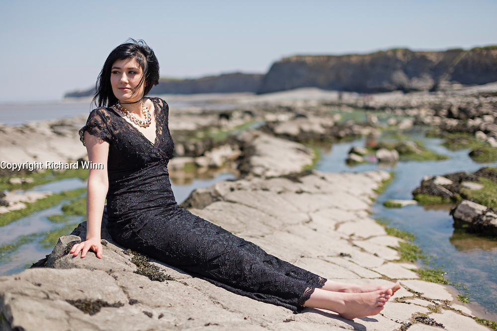 Young woman wearing a black dress in a coastal setting.