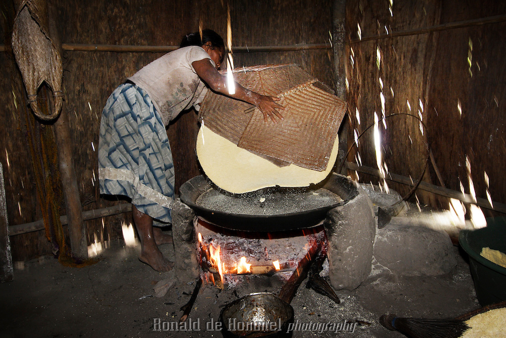 A indigenous woman Making yucca (cassava) bread in a hut on the shore of the Orinoco river. She lives in a small vilage of eight huts on the banks of the river in Aamazonas, the southern state of Venezuela. She belongs to a tribe of Curipaco Indians.