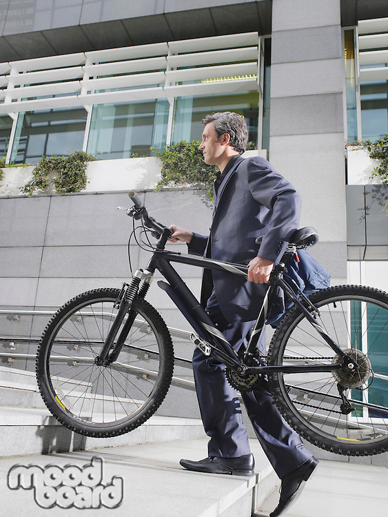 Business man carrying bicycle up steps side view