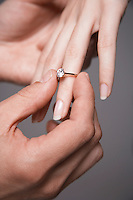 Man placing engagement ring on woman's finger close-up of hands