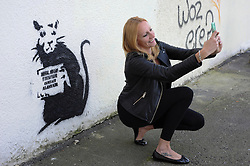 """© Licensed to London News Pictures. 31/10/2015. Folkestone, UK. SOFIE VIAENE taking a picture of artwork by the artist BANKSY, next to the location of a BANKSY piece that was removed. The Artwork pokes fun at the removal of the last piece which was called """"Art Buff"""", which was of an old lady, and says """"IF FOUND PLEASE CONTACT ALASTAIR. Alastair Upton is the Chief Executive of the Creative Foundation who as called for the picture to be returned to the town. Photo credit:Grant Falvey/LNP"""