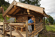 young child of two plays in a log cabin in a playground Photographed in Austria