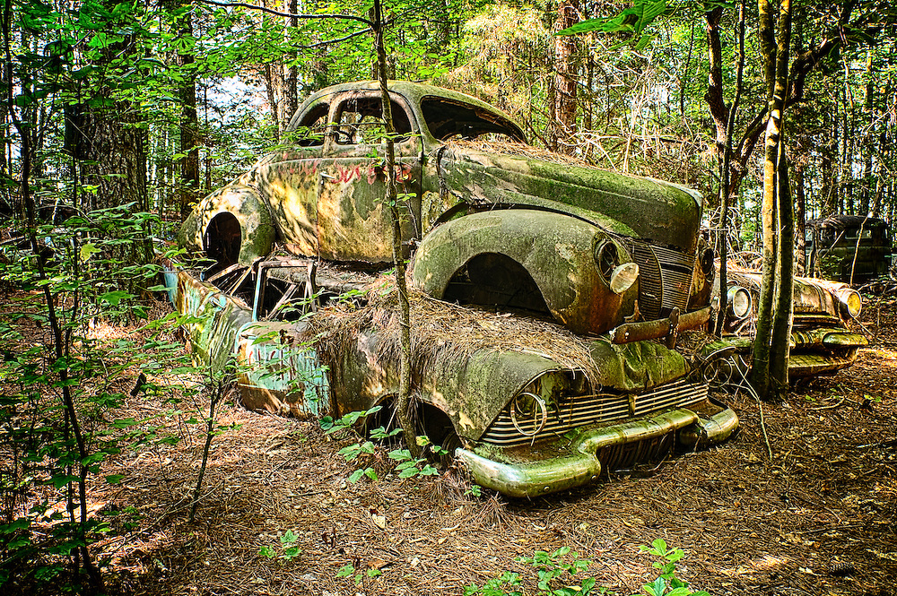 Two old, rusty cars where one car seems to be crushing the second in the Old Car City junkyard in Georgia.