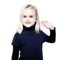 studio portrait of a caucasian cute litle girl saluting