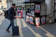 On the day that the UK Government's Chief Scientific Advisor, Sir Patrick Vallance said that the Coronavirus Covid-19 outbreak was now spreading person to person in the UK, A traveller walks past the latest news headline from the capital's London Evening Standard newspaper outside Charing Cross railway station, on 6th March 2020, in London, England.
