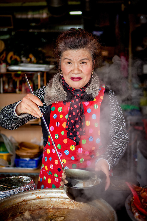 Portrait of a woman preparing a soup at Jagalchi Fish Market in Busan, South Korea.