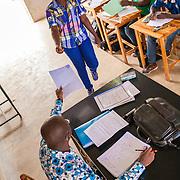 LÉGENDE: BTS génie civil 1ère année mécanique. Pendant la correction du devoir surveillé de mécanique et remises des copies aux étudiants. LIEU: CERFER, Lomé, Togo. PERSONNE(S): Le professeur corrige et remet la copie à une étudiante.