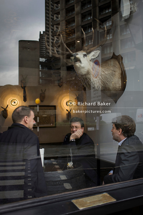 Under a mounted head and antlers of a stag, three city businessmen enjoy a lunchtime drink in a bar at the Barbican in the City of London.