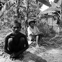 "SIEM REAP, FEBRUARY-28 : Gror Som, 54, (L) a schizophrenic patient, and his wife sit outside their hut nearby Siem Reap...One day Gror was thrown into a pond with 30 villagers and burried alive by the Khmer Rouge. By coincidence he was sniffed out at night by 2 dogs who were dragging him to a village... .The country's entire infrastructure, including the health system, was destroyed during the Khmer Rouge reign and years of civil war. Only in recent years , several non governmental organizations have helped provide mental health services and training in the country in collaboration with local healers..Mental health service is relatively new to Cambodia, but much needed. Before the Pol Pot regime Cambodia only had one mental hospital for the whole population which was destroyed during the years of horror..Modest by western standards, the first mental health clinic for all of Cambodia was set up in Siem Reap by a team from Harvard University in 1994. .This is because many refugees settled down in and around Siem Reap. 102 doctors and counsellers were trained by the Harvard specialists in the late nineties as more than 80 percent of the population was traumatized by the Pol Pot years, and even more during their years in the refugee camps. Studies have shown that most  Cambodians showed PTSD ( Posttraumatic Stress Disorder) symptoms similiar to the Jewish survivors of concentration camps. . .As for the future, Cambodians are sceptical if there'd be a fair trial for the people . It'd be very difficult to bring patients to the capital Phnom Penh to witness . Due to Cambodias underdevelopped infrastructure, many Cambodians are even not aware of the trial preparations. There's no money and also many people do not want to be reminded. says a counselor in Siem Reap:""  it only would open old wounds. People rather suffer in silence"".."