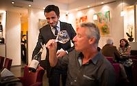 Laurent Inoue presents a bottle of wine at Les Deux Canailles.