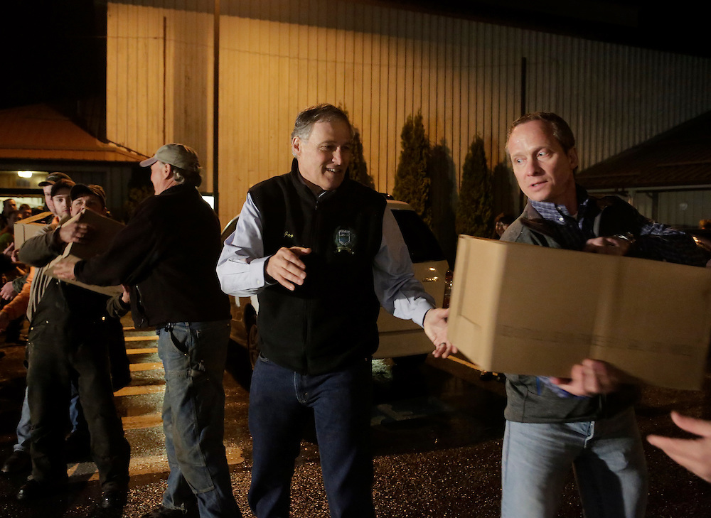Washington Governor Jay Inslee (2nd R) helps community members unload a truckload of donated goods from The Rock Church in Monroe, Washington at the Community Center in Darrington, Washington March 26, 2014. Search teams picked through mud-caked debris on Wednesday looking for scores of people still missing from a deadly Washington state weekend landslide, while local officials fended off criticism of property development in the area after previous slides. The known death toll stood at 24, with as many as 176 people still unaccounted for near the rural town of Oso, where a rain-soaked hillside collapsed on Saturday and cascaded over a river and a road, engulfing dozens of homes on the opposite bank.  REUTERS/Jason Redmond (UNITED STATES)