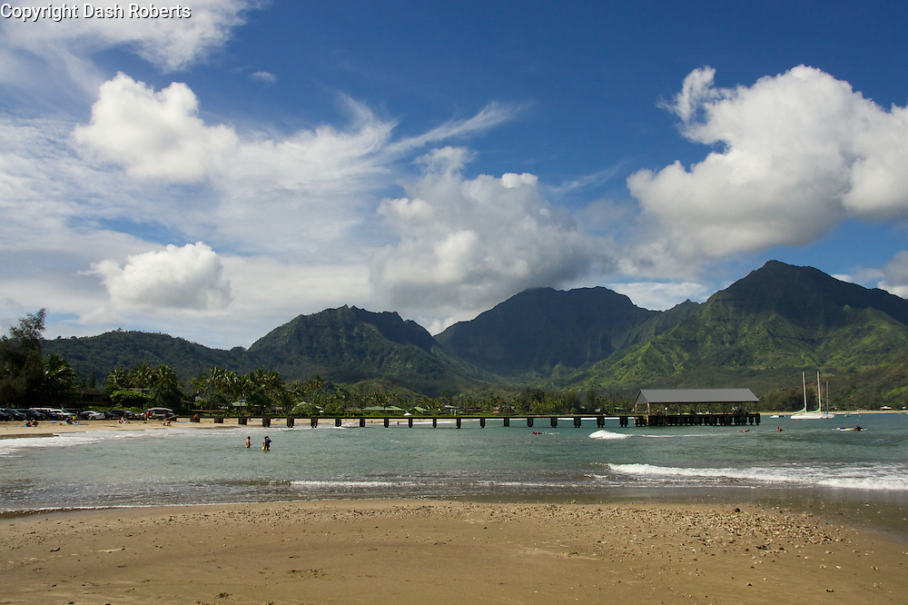 Hanalei Bay Pier with mountain range in background.
