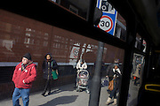 Bus passengers and city travellers are seen through a bus window as they await their next service into central London.