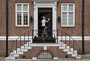 A lady polishes the front door of a fine property in Mayfair, on 8th March 2018, in London, England.