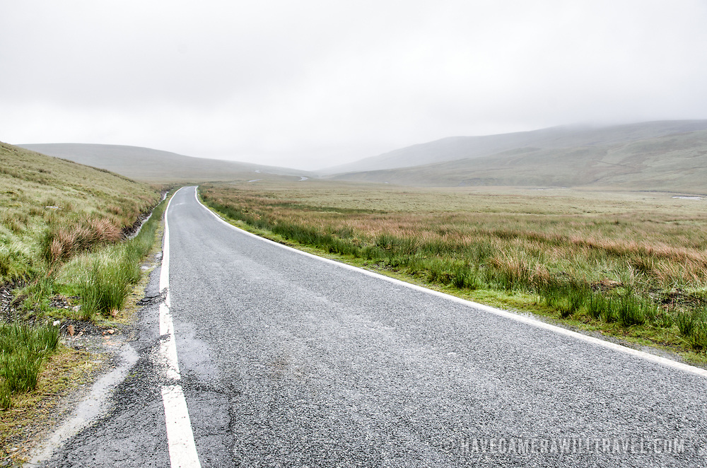 A road winds its way into the mist on a plateau in Snowdonia, Wales.