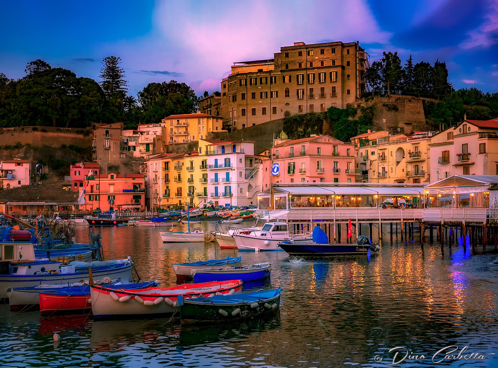 """""""Sunset at Marina Grande - Port of Sorrento""""…<br /> <br /> Arriving in Sorrento in late spring, the sunlight colorfully lingered before surrendering to the famous Sorrento moon.  One of the highlights of my Italian journey was stumbling upon the tiny Marina Grande fishing village. It was as if I'd walked back in time and merged into this ageless world with its own pace and traditions. Life here seemingly has its own rhythm- a strongly united community tenaciously anchored to its family principles, hard work, and religious traditions. They love the sea and live in symbiosis with it; here time seems to move more slowly than anywhere in the world.  In 1558 the Turks plundered the town of Sorrento, and after the Saracens left the inhabitants constructed a solid town wall. My eyes were blessed with an extraordinarily beautiful canvas as a permanent smile measured my face, and my camera gazed upon this tiny bay nestled within the bygone fishing village.  I meandered about cautiously, glancing at fisherman humbly repairing their nets.  At the heart of the Marina is the Church of Sant'Anna, patron saint of the village. Restaurant Zi' Ntonio a Mare, which jutted out into the bay, was crowded with hungry guests and serenaded by an Italiano singer who, ironically, was singing Dean Martin songs which echoed throughout the bay;  guests and this photographer were delightfully enchanted.  I gently creeped along the water's edge, and tried to capture the perfect, yet very personal portrait of this piccola baia italiana della perfezione (Italian small bay of perfection).  As night fell, the water reflections and resting fishing boats posed for a few more images as fish jumped for their dinner!  It was time to enjoy the gifts of the day's catch at Ristorante di """"Zi'Ntonio Mare.  The epicureo delights, especially the calamari, olive bread, wine, and the main course of Il pesce San Pietro (The St. Peter's fish), was authentic perfection…just like this perfect piccola bay of Marina Gran"""