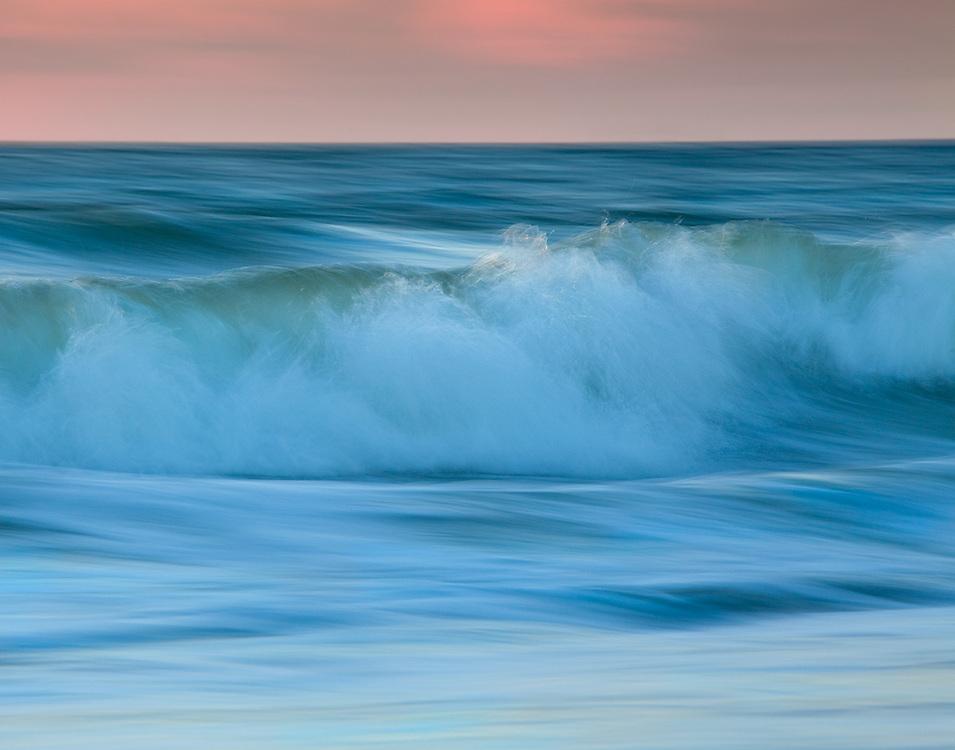 A breaking wave at dawn crashing towards the shore.