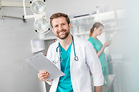 Portrait of smiling doctor holding clipboard while standing against coworker at veterinary clinic