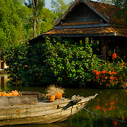 Old Thai style river barge in front of a thai style house at Muang Borang in Samut Prakarn, Thailand.