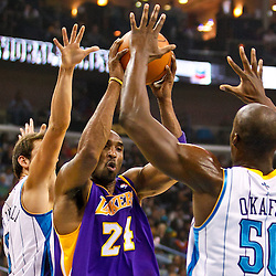 December 29, 2010; New Orleans, LA, USA; Los Angeles Lakers shooting guard Kobe Bryant (24) drives between New Orleans Hornets center Emeka Okafor (50) and shooting guard Marco Belinelli (8) during the first quarter at the New Orleans Arena.   Mandatory Credit: Derick E. Hingle