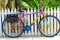 Rainbow coloured bicycle against white picket fence, Key West Florida
