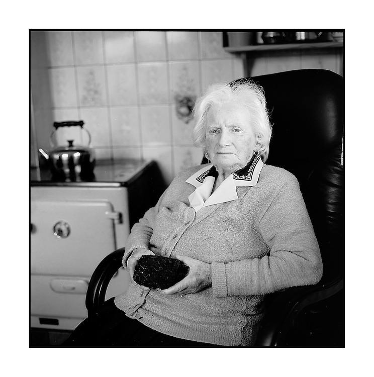 Bernadette Morrisson sits in her kitchen by the range with an old sod of turf that her husband cut from Mouds bog before he died. All cutting on the bog is to cease by the end of 2011. Photo: Kim Haughton