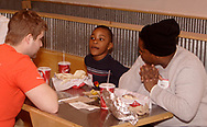 Kathy Charles (right) listens as her son Anthony, 6, talks to Pat Tramonte at a burrito party for the homeless hosted by U.D. Religious Studies student Joe Melendrez at Chipotle's on Brown Street in Dayton.