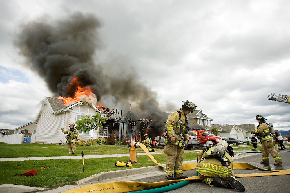 JEROME A. POLLOS/Press..Coeur d'Alene firefighters connect fire hoses to a hydrant before attacking a house fire Monday in Hayden. The home was completely destroyed by the blaze that started in the garage of the rental home.