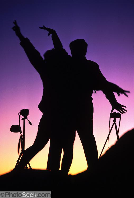 Photographers flourish in silhouette against a magenta and orange sunset in the High Sierra, California, USA. Published in Modern Photography Magazine February 1987.