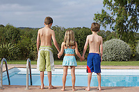 Two boys and girl (6-11) standing on edge of pool back view
