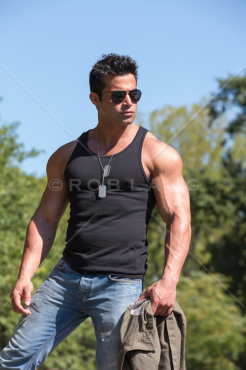 rugged muscular army man in a tank top and sun glasses outdoors