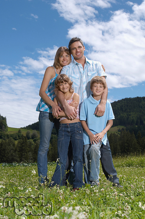 Parents with children (7-9) embracing in field portrait