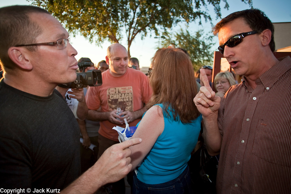 "Aug 10, 2009 -- CHANDLER, AZ: An opponent of health care reform (left) confronts a supporter of health care reform (right) during a health care reform meeting in Chandler, AZ. Rep. Jeff Flake, (R-AZ) hosted a ""town hall"" style meeting on health care reform at Basha High School in Chandler Monday. Flake, a conservative Republican, has opposed President Obama on many issues, like the stimulus and health care reform. Protestors who have shut down similar meetings hosted by Democrats, gave Flake a warm welome. About 1,600 people attended the meeting.   Photo by Jack Kurtz"