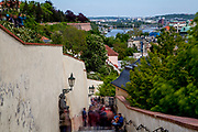 """Tourist groups and visitors walking from Prague Castle via the Old Castle Stairs (Stare zamecke schody) down to the center of  """"Lesser Town"""" (Mala Strana)."""