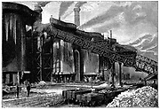 Blast furnaces, Barrow Haematite Iron and Steel Company, Barrow in Furness, Lancashire (Cumbria). Charge being taken to top of furnace on railway. In foreground are railway trucks transporting ore and fuel.   Wood engraving 1890
