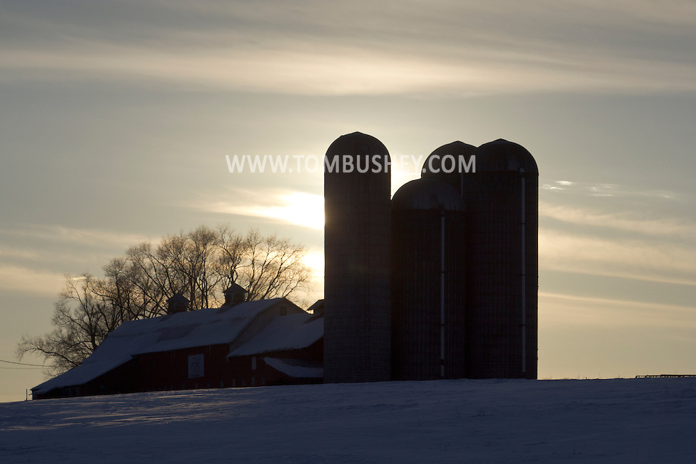 Goshen, New York - The sun sets behind a barn and silos on a farm Feb. 10, 2013.Winter farm scene