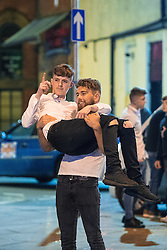 """© Licensed to London News Pictures . 24/12/2016 . Manchester , UK . A man carries another outside The Birdcage nightclub . Revellers out in Manchester City Centre overnight during 2016's second """" Mad Friday """" , named for historically being one of the busiest nights of the year for the emergency services in the UK . Photo credit : Joel Goodman/LNP"""