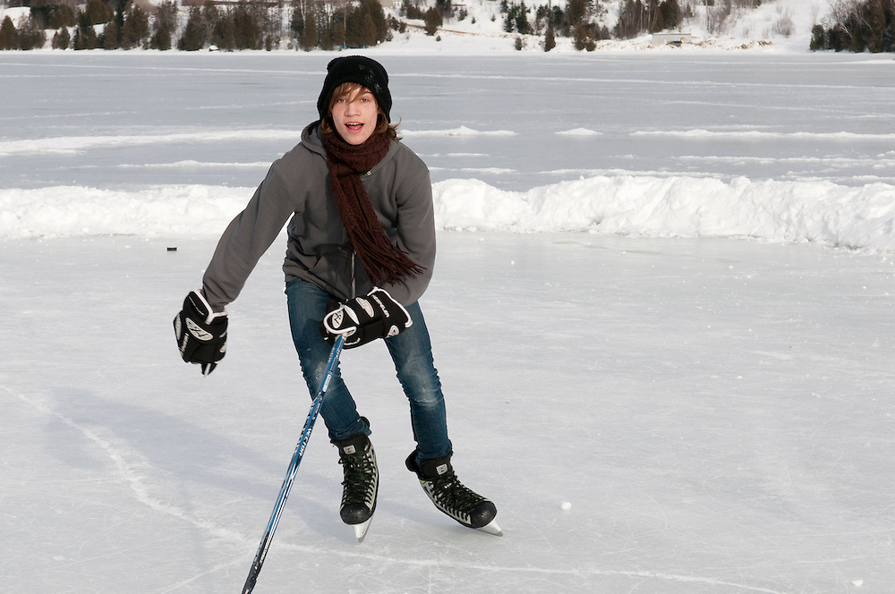 Boys playing hockey for fun on a lake during winter in Quebec