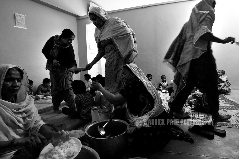 Caregivers at the Edhi orphanage serve lunch to the children on February 1, 2008 in Karachi, Pakistan. The Edhi Foundation urges women give up unwanted children rather than abandon or kill in order to cover up children conceived out of wedlock, or through rape. The Edhi Foundation orphanages represent a microcosm of Pakistan's absolute poverty where children are its first casualty, tragedy and hope collide on a daily basis, and life and death are in constant flux existing only rooms apart. Pakistan is a country more than a third of it's population live in absolute poverty. As world attention fixates on Pakistan's ongoing political turmoil, generations of children are being abandoned due to Pakistan's spiraling poverty and growing instability. Some are born out of wedlock - a major social taboo - others discarded due to physical and mental disabilities, but nearly all are abandoned due to poverty. Boys and girls alike are abandoned every year, found in dumpsters mauled by rats and dogs, or left to fend for themselves on the streets of Karachi's sprawling and unforgiving metropolis. The lucky ones find their way to the Edhi Foundation orphanages. (Photo by Warrick Page)