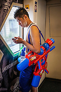 13 APRIL 2014 - BANGKOK, THAILAND: A Thai man armed with squirt guns on the BTS Skytrain in Bangkok on the first day of Songkran. Songkran is celebrated in Thailand as the traditional New Year's Day from 13 to 16 April. Songkran is in the hottest time of the year in Thailand, at the end of the dry season and provides an excuse for people to cool off in friendly water fights that take place throughout the country. Songkran has been a national holiday since 1940, when Thailand moved the first day of the year to January 1.    PHOTO BY JACK KURTZ
