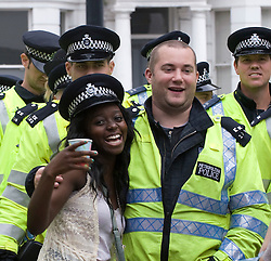 © Licensed to London News Pictures. 29/08/2011. London, UK. A lady poses with police officers  during  day 2 of the 2011 notting Hill Carnival today (29/08/2011) the second largest street festival in the world after the Rio Carnival held in Brazil . Photo credit: Ben Cawthra/LNP
